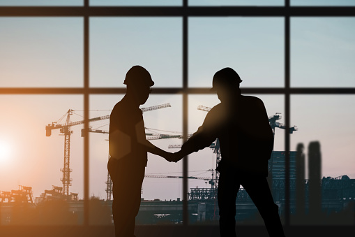 Silhouette of engineer and construction team working at site over blurred background for industry background with Light fair.Create from multiple reference images together 1050723768