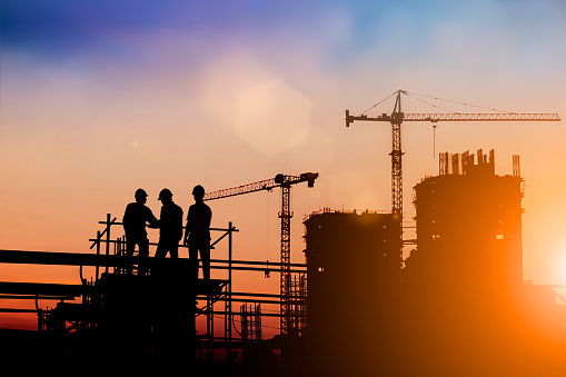 Silhouette of engineer and construction team working at site over blurred background for industry background with Light fair.Create from multiple reference images together 1162046065