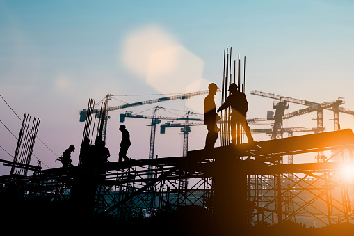 Silhouette of engineer and construction team working at site over blurred background sunset pastel for industry background with Light fair.Create from multiple reference images together. 981344368