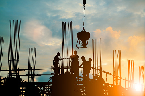 Silhouette of engineer and construction team working safely work load concrete on scaffolding on high rise building. over blurred background sunset pastel for industry background with Light fair 838476004