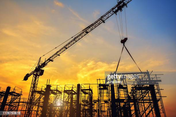 silhouette of engineer and safety officer looking construction worker pouring a concrete column on scaffolding in construction  site - kran stock-fotos und bilder