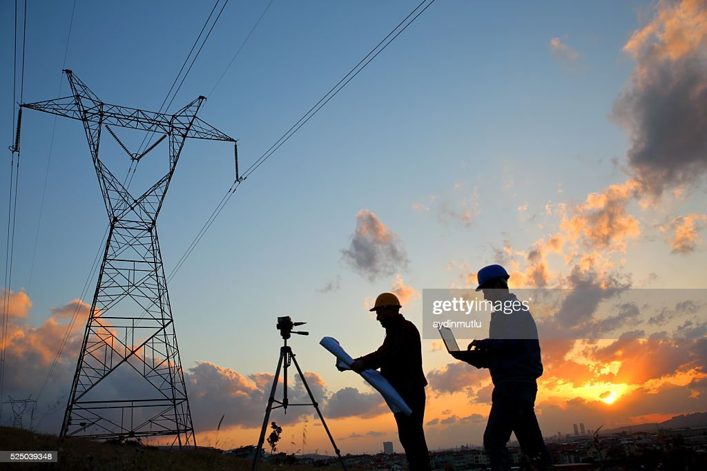 Silhouette of engineers workers at electricity station : Stock Photo