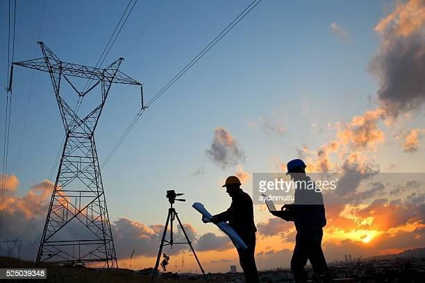 silhouette of engineers workers at electricity station - power line stock pictures, royalty-free photos & images