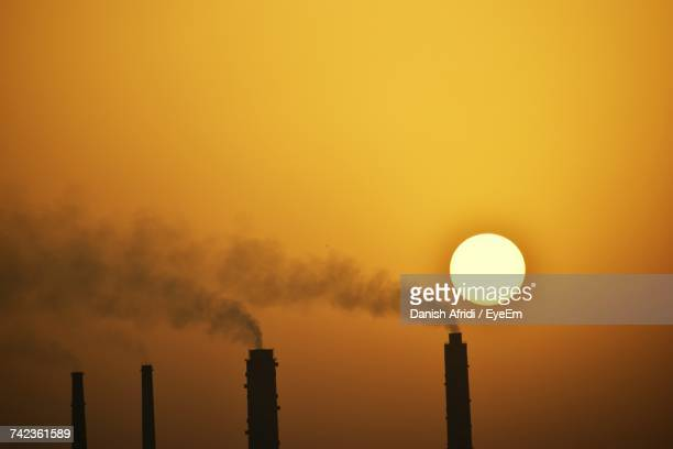 Silhouette Of Factory Against Sky During Sunset