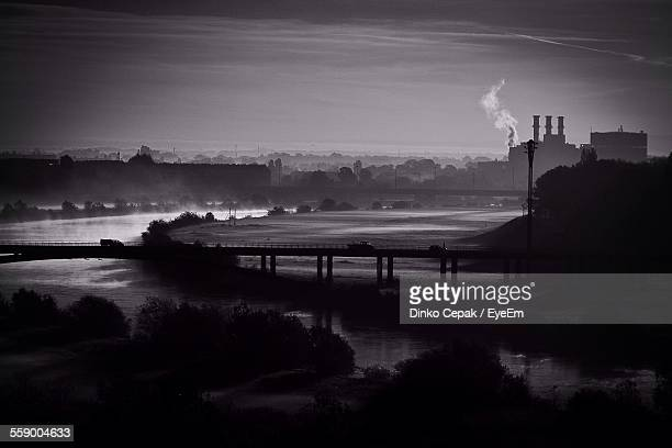 Silhouette Of Factory By River