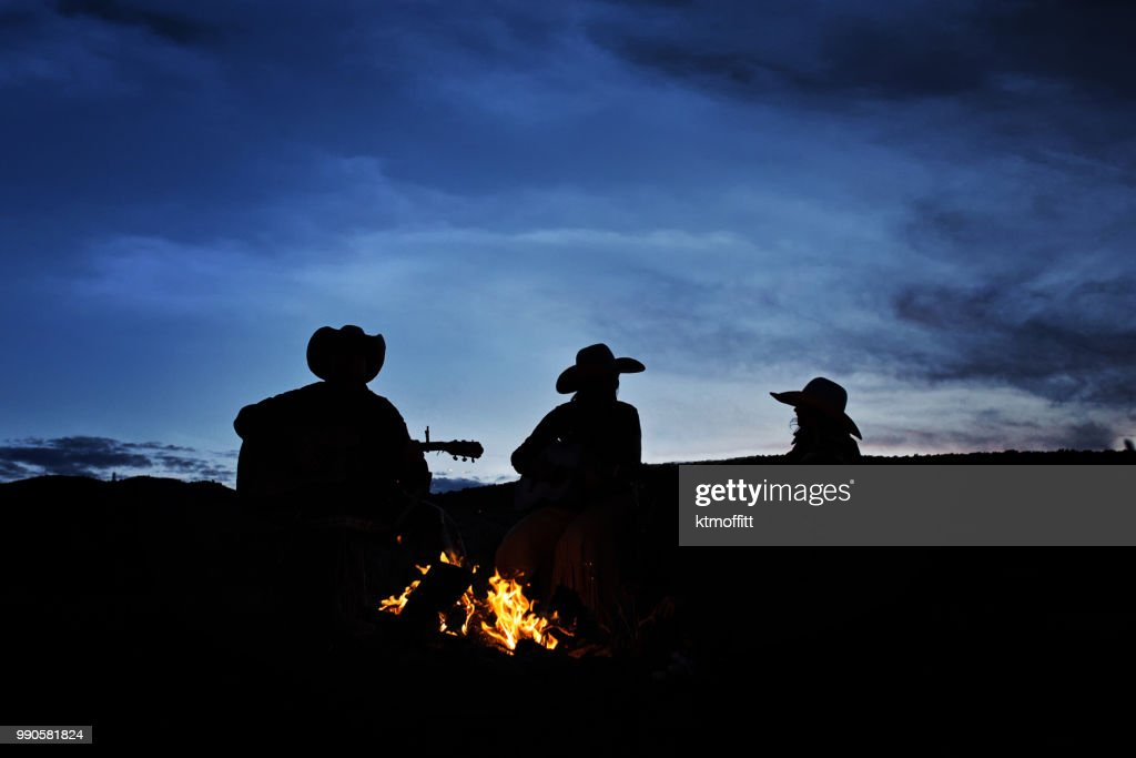 Silhouette of Family At Campfire Listening to Guitar : Stock Photo