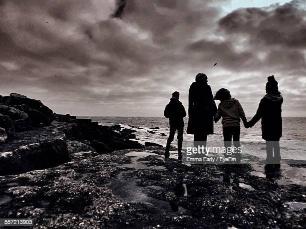 Silhouette Of Family Standing At Beach Coastline