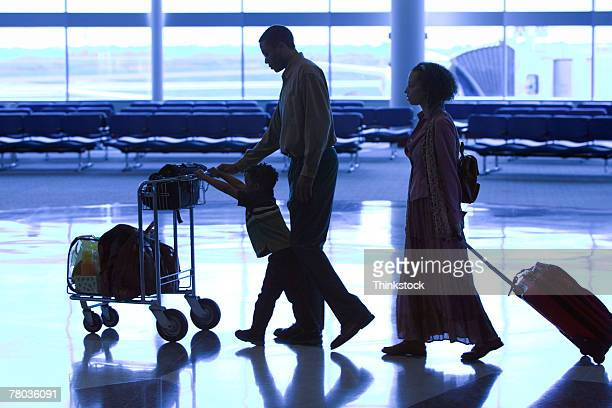 Silhouette of family walking through airport