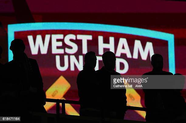 Silhouette of fans standing in front of the West Ham badge during the EFL Cup fourth round match between West Ham and Chelsea at The London Stadium...