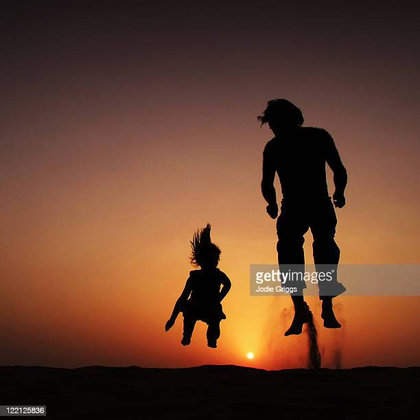 Silhouette of father and child jumping at sunset