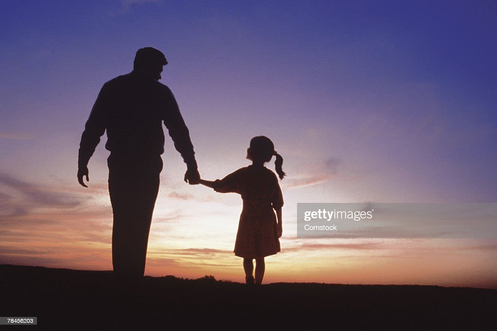 Silhouette of father and daughter walking : Stock Photo