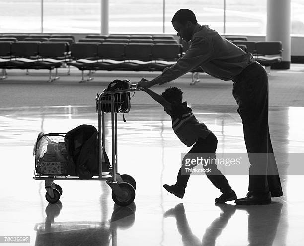 Silhouette of father and son walking through airport
