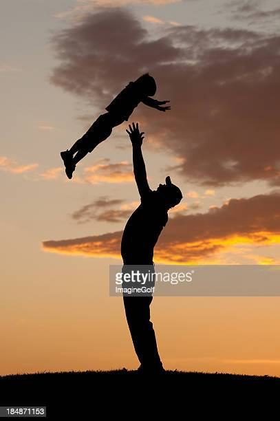Silhouette of Father Throwing Child in the Air Playing