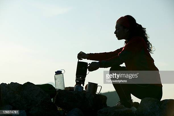 Silhouette of female camper stirring pot, in the Lake District