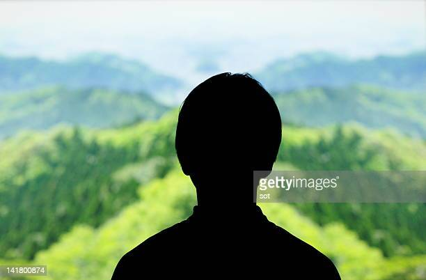 Silhouette of female looking at the green mountain