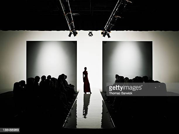 silhouette of female model on catwalk - catwalk stock pictures, royalty-free photos & images