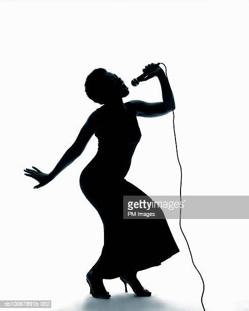 Silhouette of female singer singing on microphone