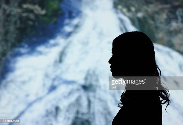 Silhouette of female standing in waterfall