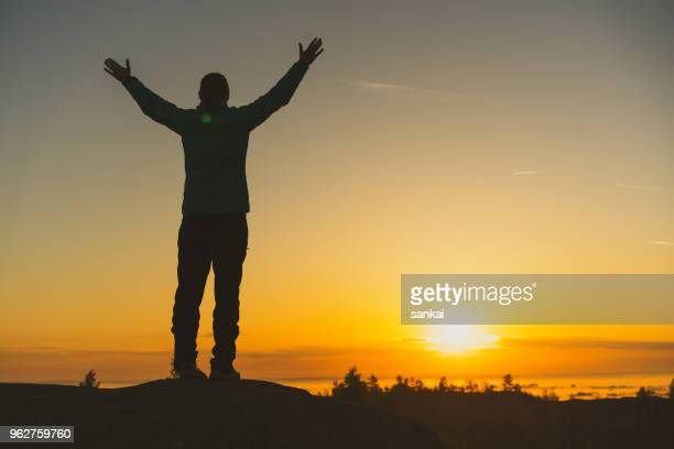 silhouette of female traveler on top of the mountain at sunset - corona sun stock pictures, royalty-free photos & images