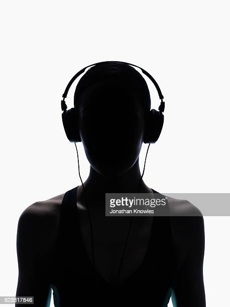 Silhouette of female with headphones, white background