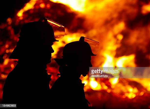 silhouette of firefighters against large fire in the dark - firetruck stock photos and pictures