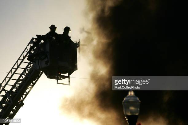silhouette of firemen in a basket lift - firetruck stock photos and pictures