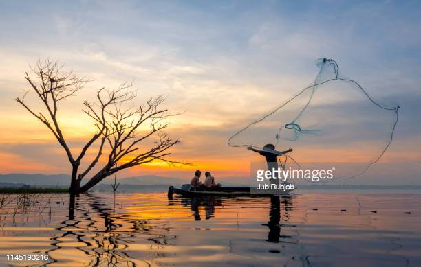 silhouette of fisherman and his family boys, sitting on fishing boat, throwing fishing net catching freshwater fish in nature river - myanmar stock pictures, royalty-free photos & images