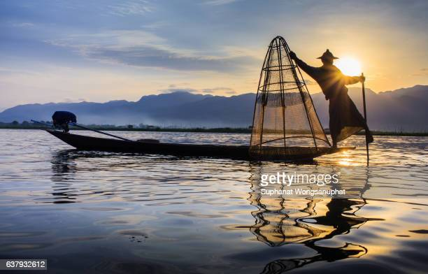 silhouette of fisherman at sunset inle lake burma myanmar - inle lake stock pictures, royalty-free photos & images