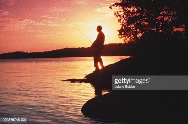 Silhouette of fisherman by lake, sunset