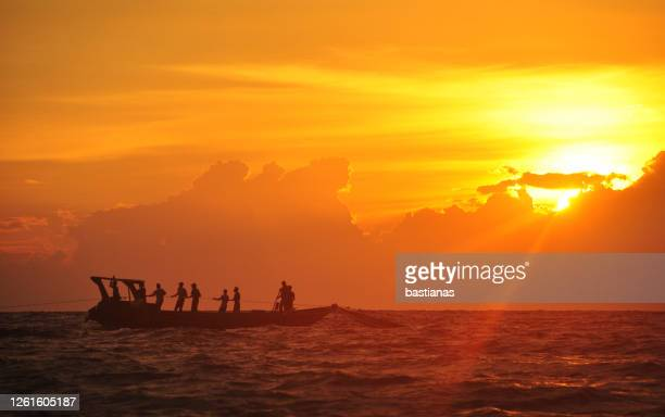 silhouette of fisherman fishing at sunset, indonesia - golden hour stock pictures, royalty-free photos & images