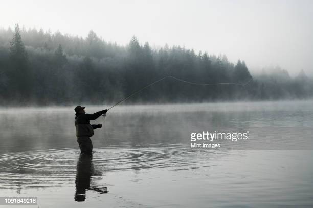 Silhouette of fisherman fly fishing for salmon and sea run cutthroat trout