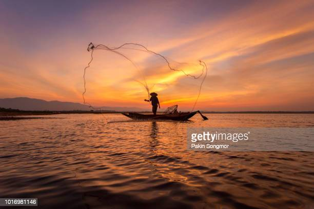 silhouette of fishermen in a boat on the lake at beautiful sunset background - asiatisches langboot stock-fotos und bilder