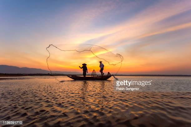 Silhouette of fishermen in a boat on the lake at beautiful sunset background.