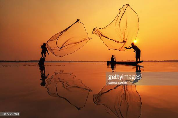 Silhouette of fishermen in action when fishing, Thailand