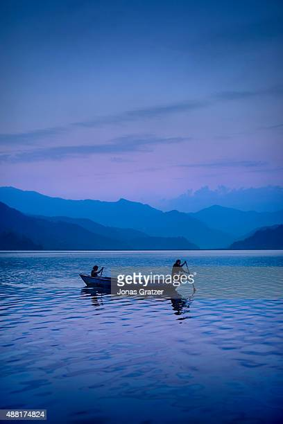 Silhouette of fishermen on a boat on the lake during the sunset. Phewa Lake is a freshwater lake in Nepal located in the south of the Pokhara Valley...