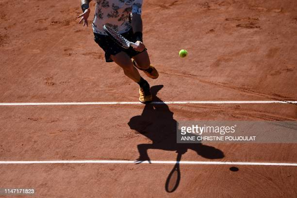 Silhouette of France's Corentin Moutet as he returns the ball to Argentina's Juan Ignacio Londero during their men's singles third round match on day...