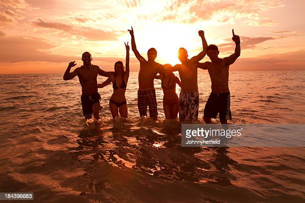 A silhouette of friends in the sea at sunset