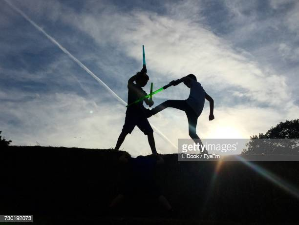 silhouette of friends playing with laser sword against sky - lightsaber stock pictures, royalty-free photos & images