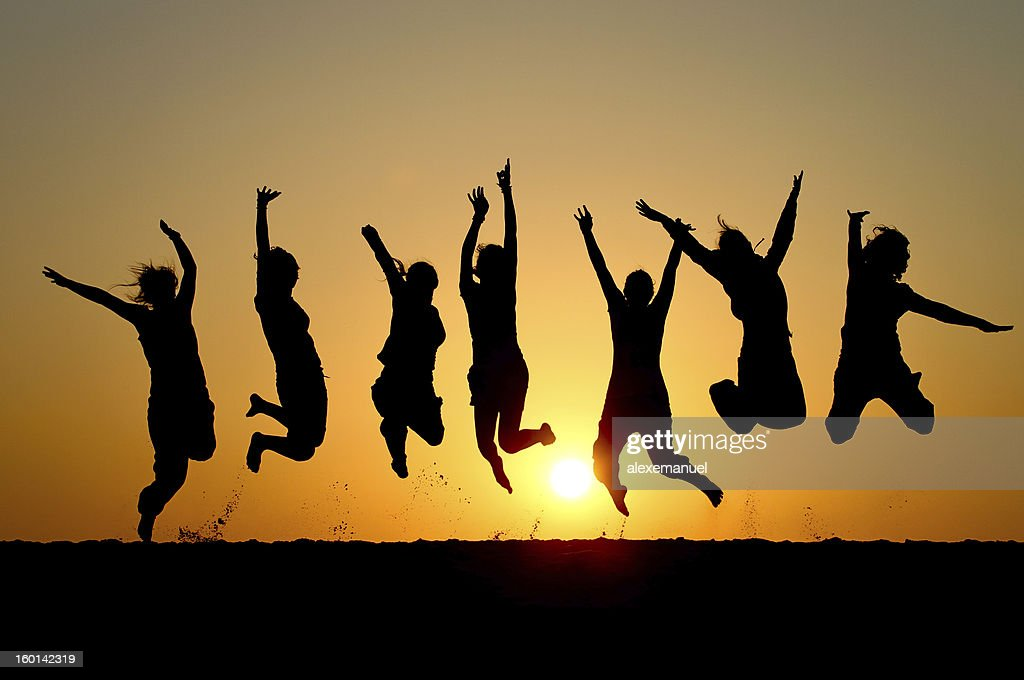 Silhouette of friends simultaneously jumping