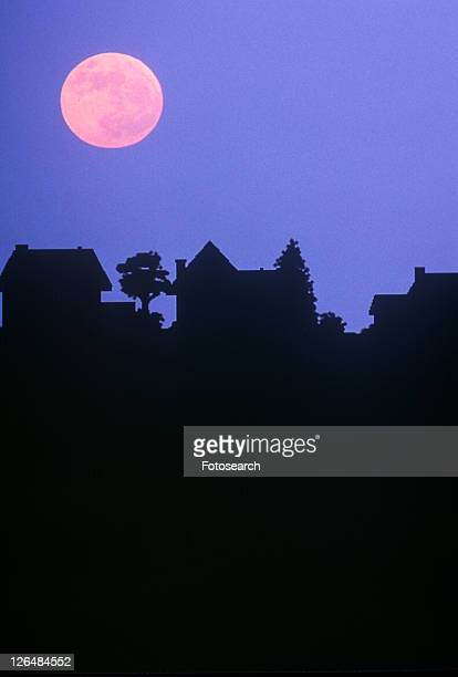 silhouette of full moon over family homes - pink moon stock pictures, royalty-free photos & images