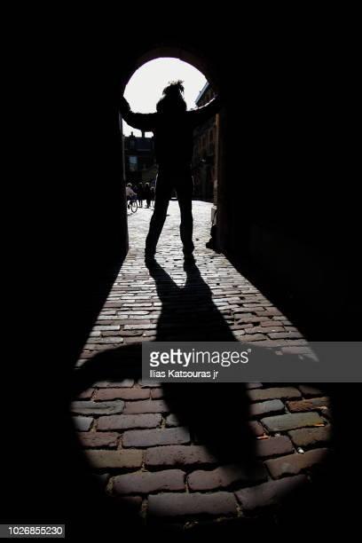 silhouette of girl blocking door, long shadow - den haag stock-fotos und bilder
