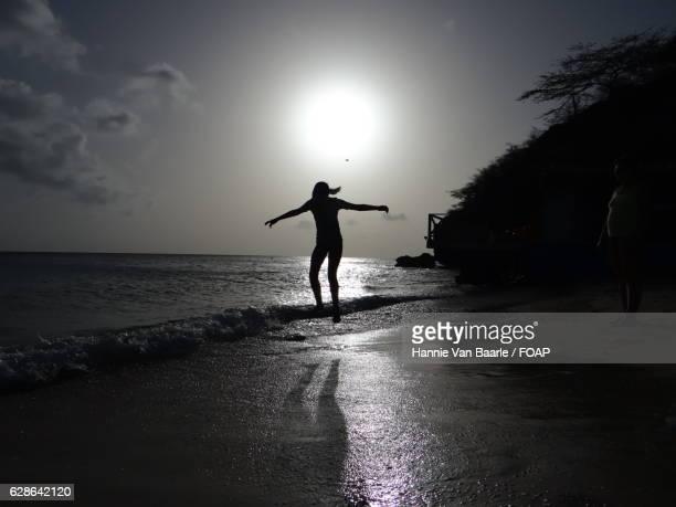 Silhouette of girl jumping in ocean