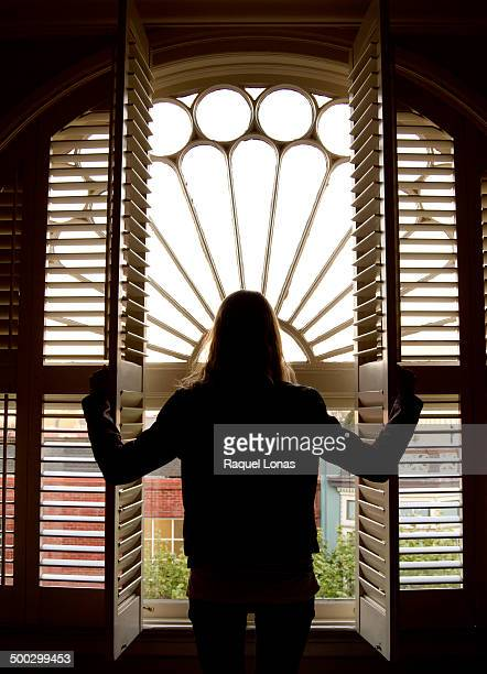 Silhouette of girl looking out window