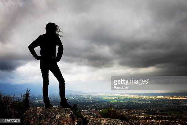 Silhouette of girl under stormy sky looking towards sunlit area