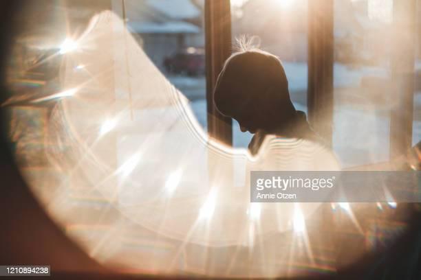 silhouette of glowing boy in front of window - ombra in primo piano foto e immagini stock