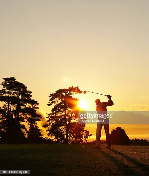 Silhouette of golfer swinging club on golf course at sunset
