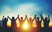 Silhouette of group business team making high hands over head in sunset sky