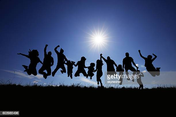 Silhouette of group of people jumping against the blue sky.