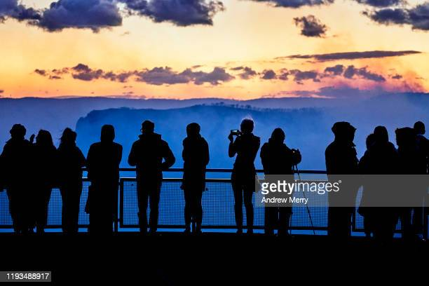 silhouette of group of tourists on viewing platform looking at bushfires in blue smoke filled valley at dusk, blue mountains, australia - blue mountains national park stock pictures, royalty-free photos & images