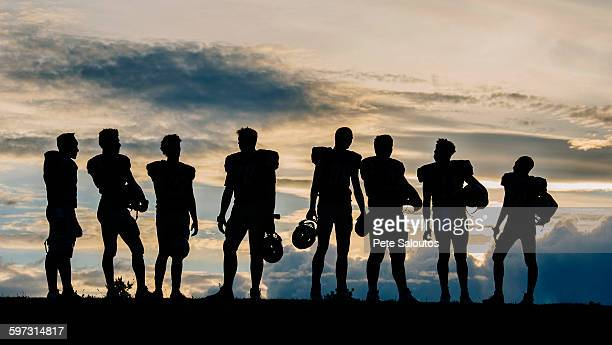 silhouette of group of young american football players, standing in row - スポーツユニフォーム ストックフォトと画像